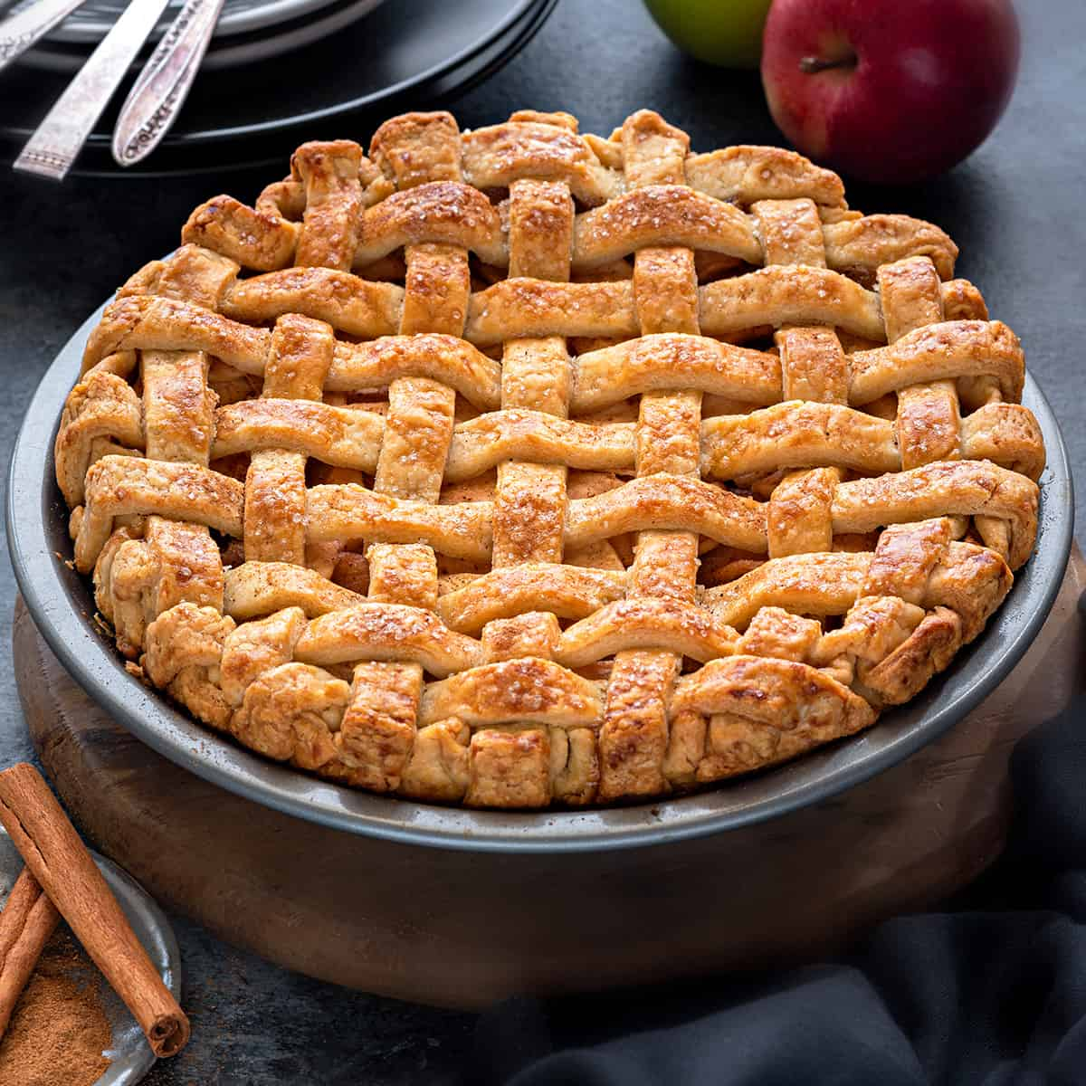 Close up shot of an apple pie with a crispy lattice crust placed in a dish