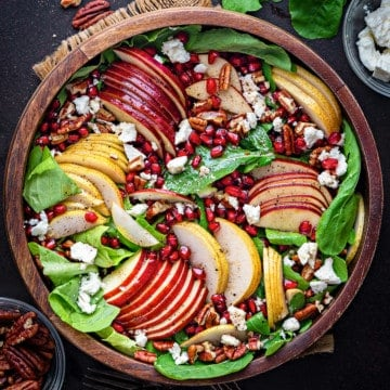 Completed arugula apple pear pomegranate harvest fall salad in wooden serving bowl.