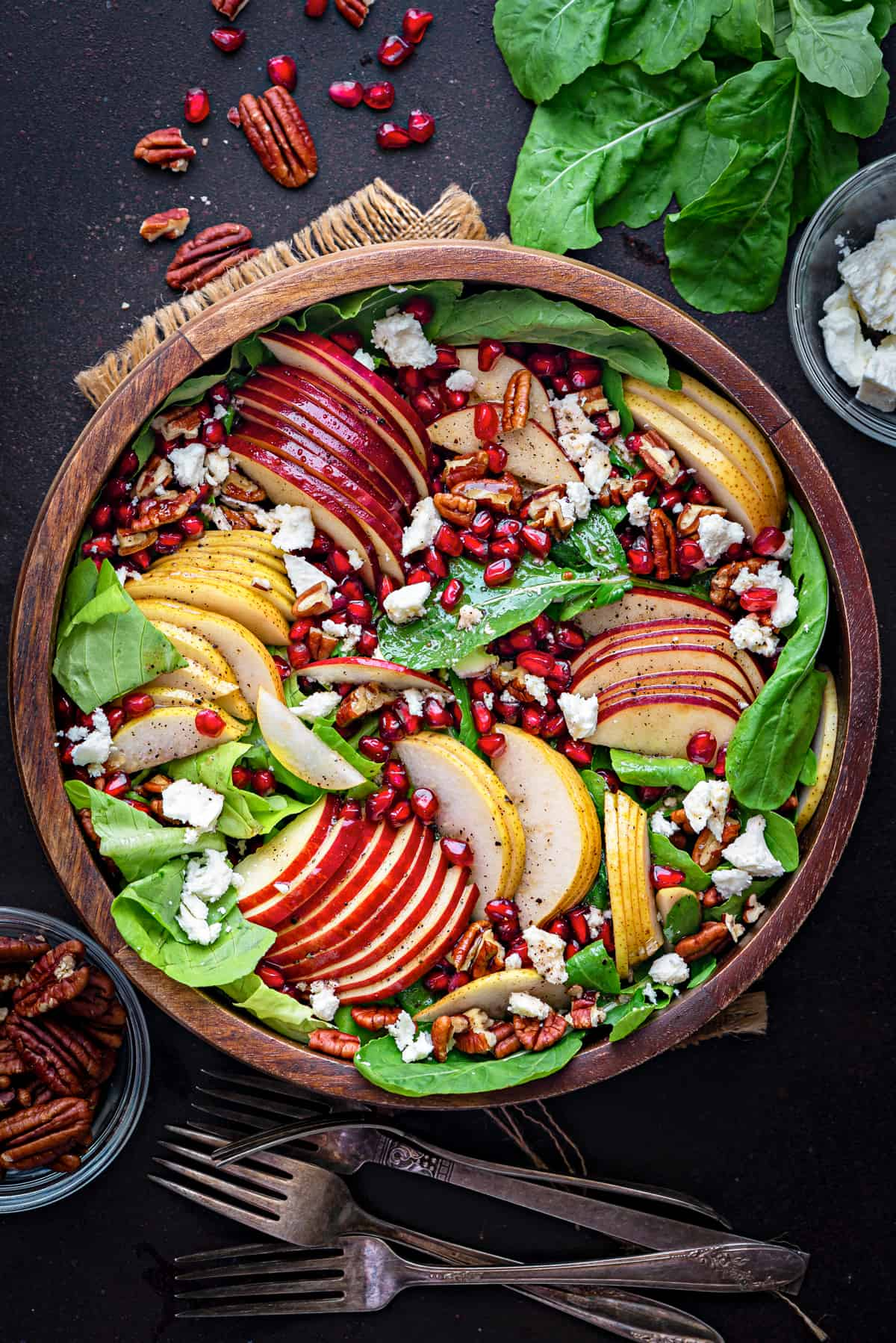 assembled autumn harvest fall salad in a wooden serving bowl with red apples slices, golden pears