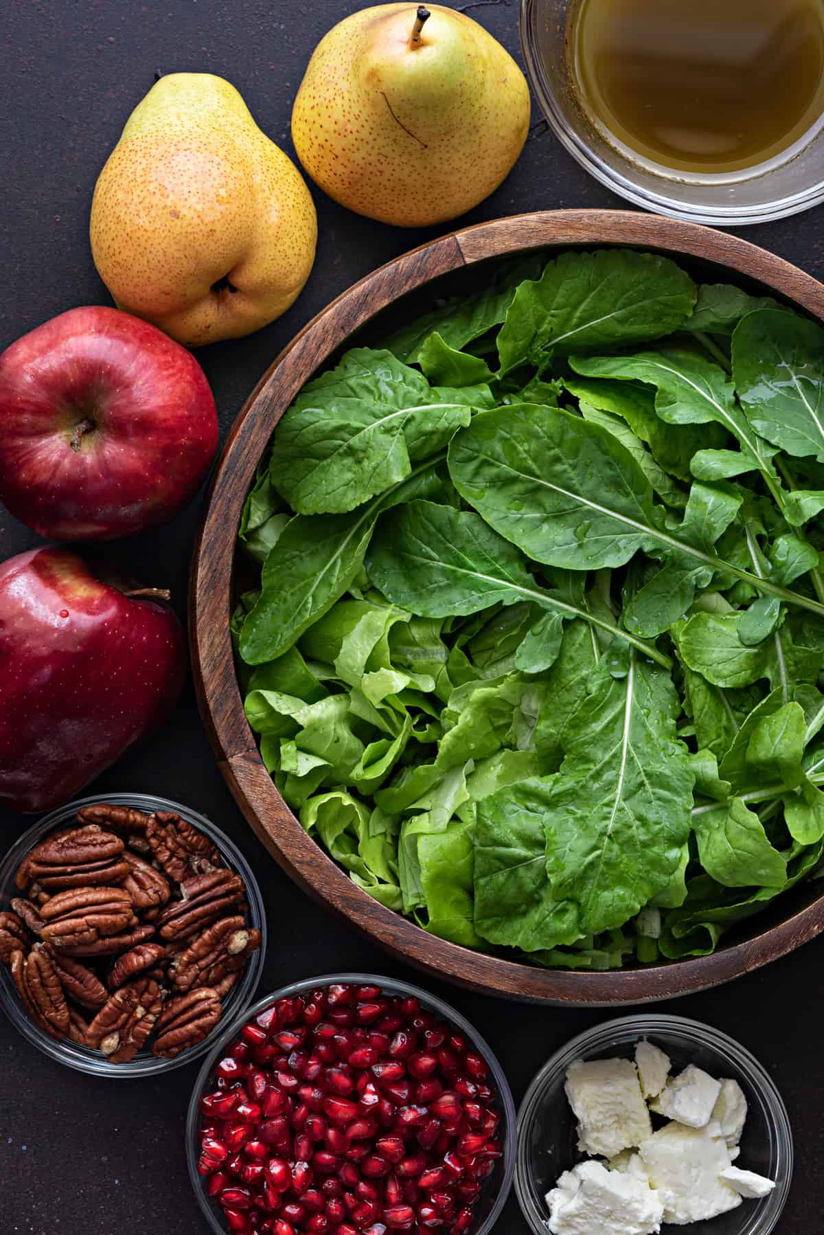 fresh spinach and rocket mix in a wooden bowl with fall salad mis en place surrounding it