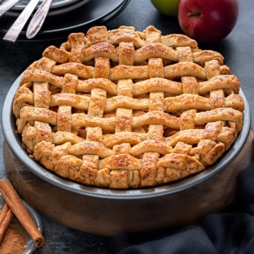 An apple pie, shot from slightly above, with a crispy lattice crust, apples placed in the background.