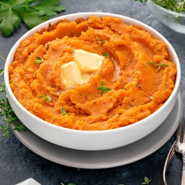 mashed sweet potatoes in a white bowl topped with butter and fresh herbs