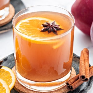 Closeup shot of homemade apple cider drink served in glass, some whole spices spread around