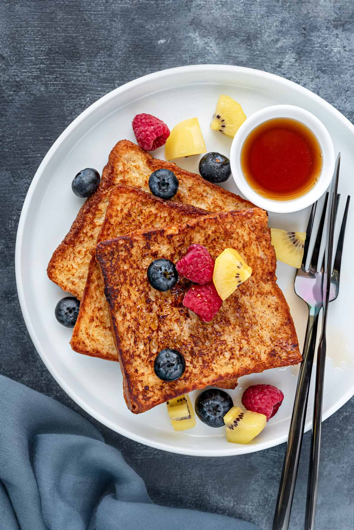 Classic brioche french toast on a round white plate with silverware, maple syrup and fresh fruits.