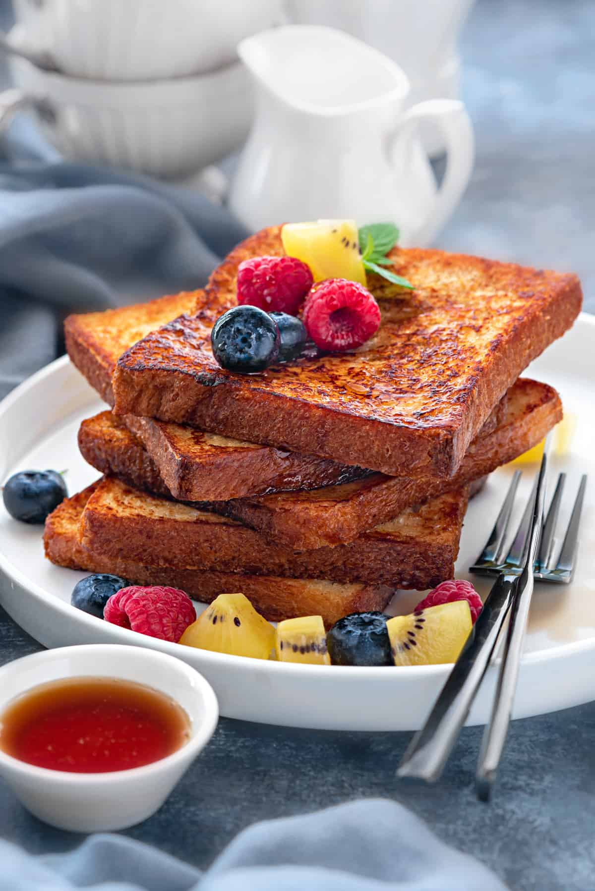 Stack of 5 slices of brioche french toast on a white plate topped with fresh fruits.