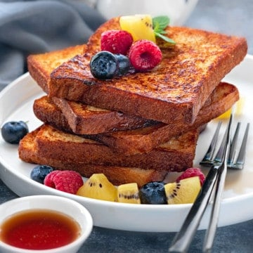 Stack of 5 slices of brioche french toast on a white plate topped with fresh fruits