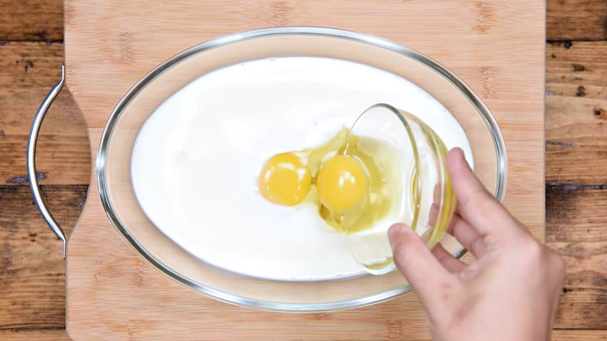 hand pouring eggs into milk in a mixing dish