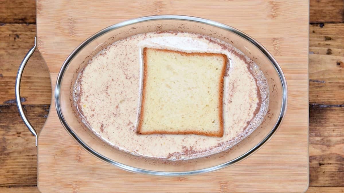 slice of brioche soaking in custard mixture for easy french toast recipe