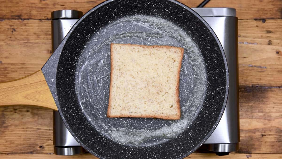 custard soaked bread added to a skillet with butter