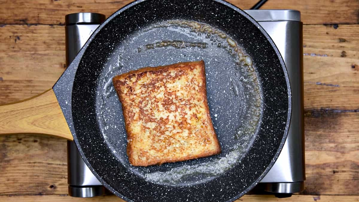 slice of french toast after being flipped in pan