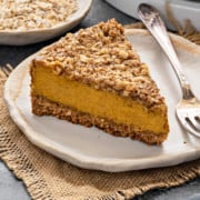 Close-up shot of pumpkin cheesecake slice placed with fork on white plate