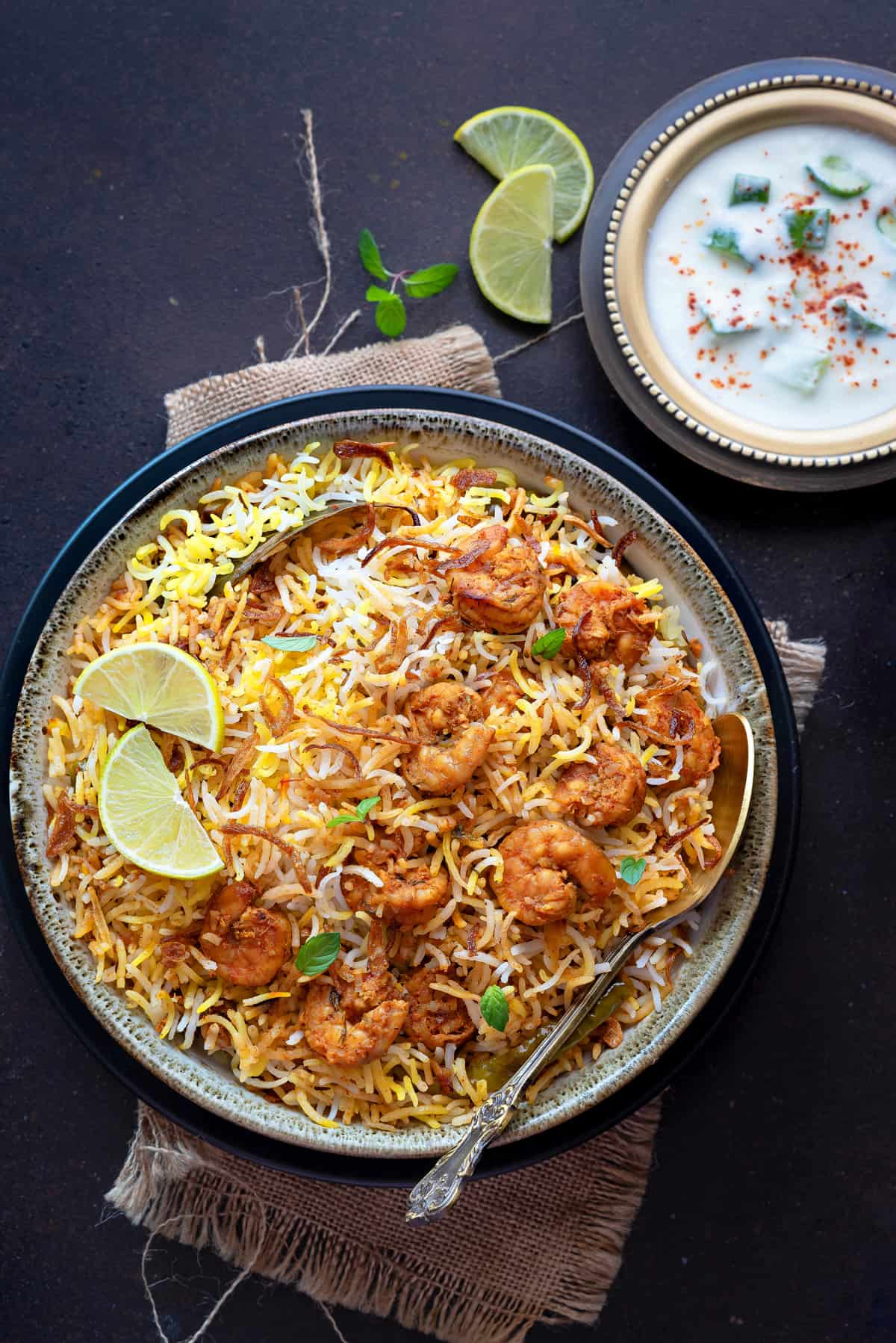 Overhead shot of prawn biryani in bowl with a spoon and yogurt raita on the side.