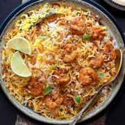 Closeup of Prawn biryani served in ceramic bowl with spoon into it.