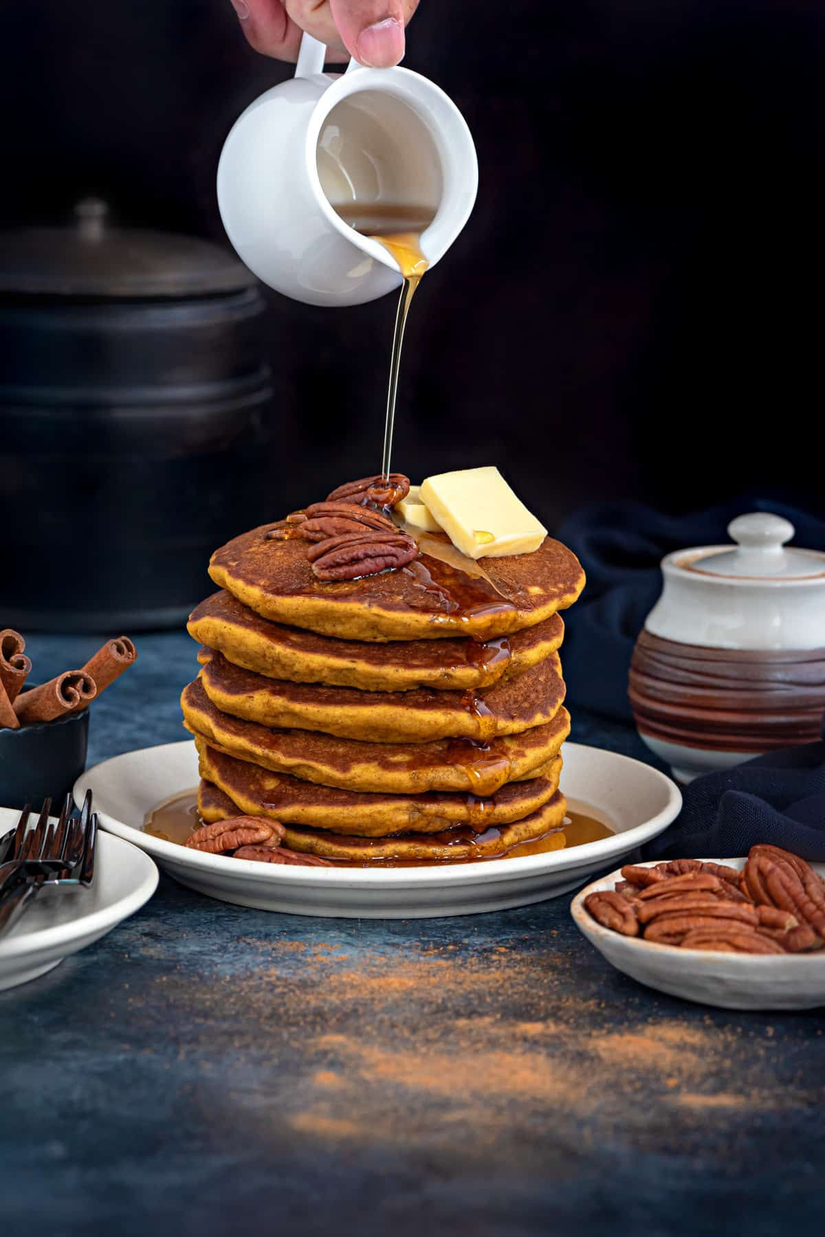 stack of pumpkin pancakes on a white plate with a hand pouring maple syrup over them