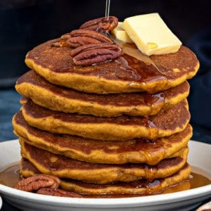 Short stack of healthy pumpkin pancakes topped with pads of butter, pecans and maple syrup