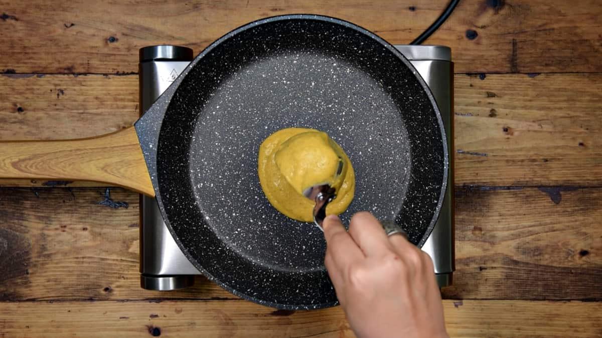 hand spooning healthy pumpkin pancake batter into nonstick pan