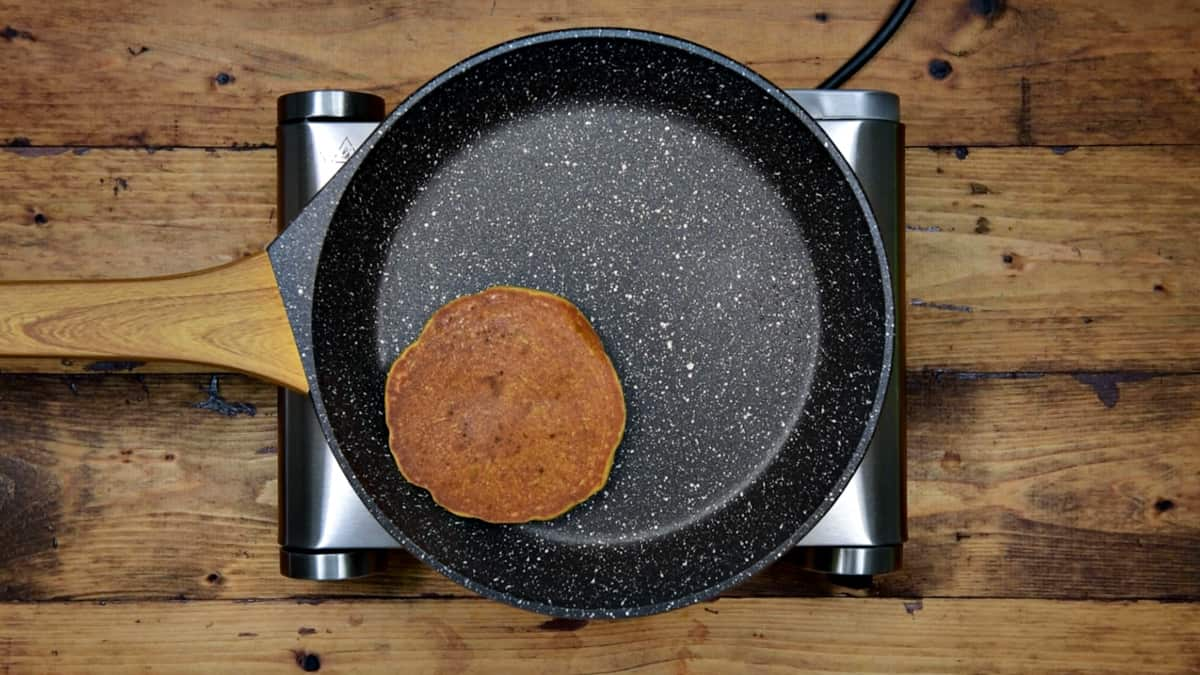 pumpkin spice pancake in a non-stick pan after being flipped
