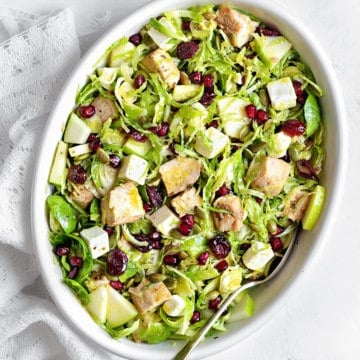 Overhead shot of shaved brussels sprouts salad in a white oblong serving dish on a white tabletop with a white linen and a silver spoon
