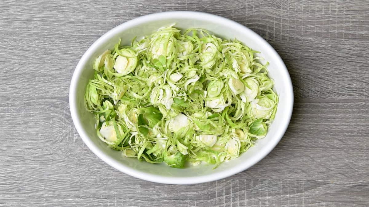 raw shaved brussel sprouts in a white oval dish