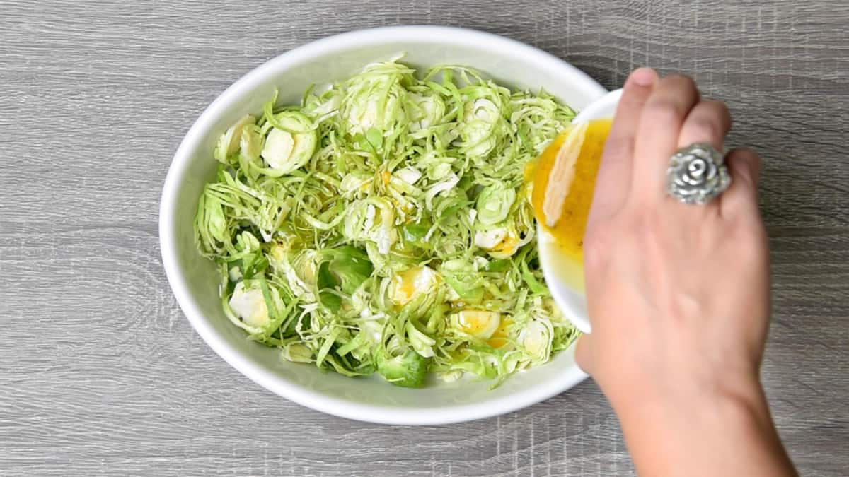 hand pouring apple cider vinaigrette over shredded raw brussels sprouts