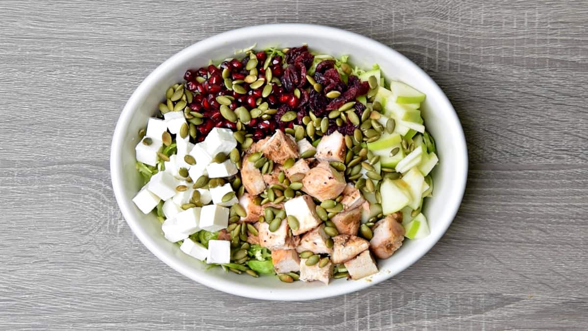 shaved brussels sprouts topped with feta cubes, pomegranate, cranberries, toasted pepitas, chicken and apples prior to tossing