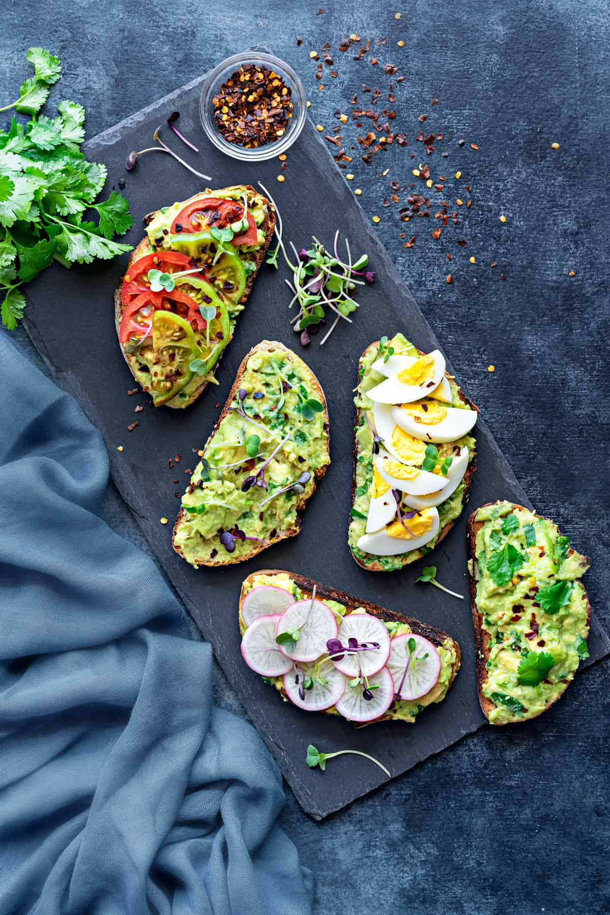 overhead shot of avocado toast with different topping ideas - microgreens, boiled egg, sliced radishes, and tomatoes