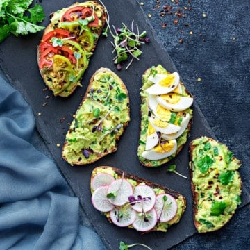 overhead shot of avocado toast with different topping ideas - boiled egg, sliced radishes, and tomatoes
