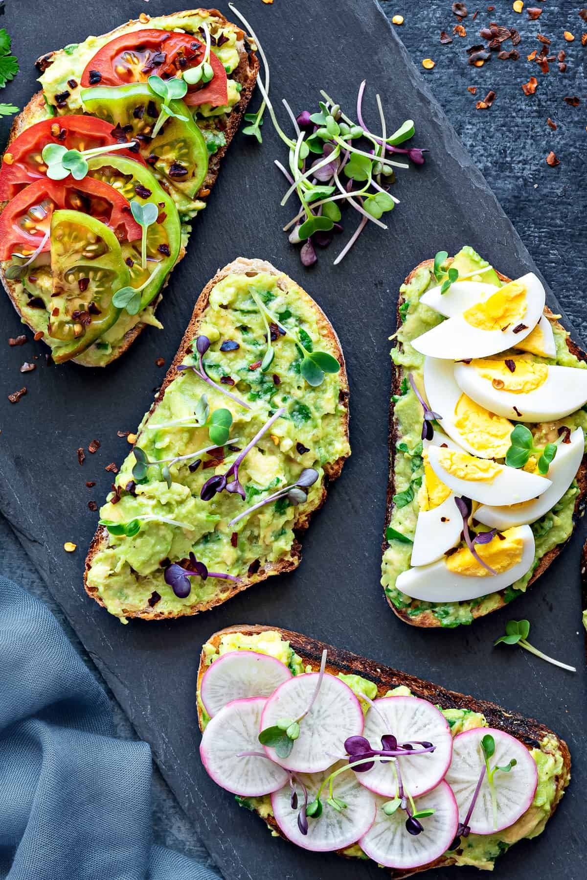 overhead shot of four slices of avocado toast with different toppings on a black slate serving tray