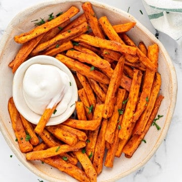 baked sweet potato fries in a cream colored bowl with a small dipping bowl of aioli