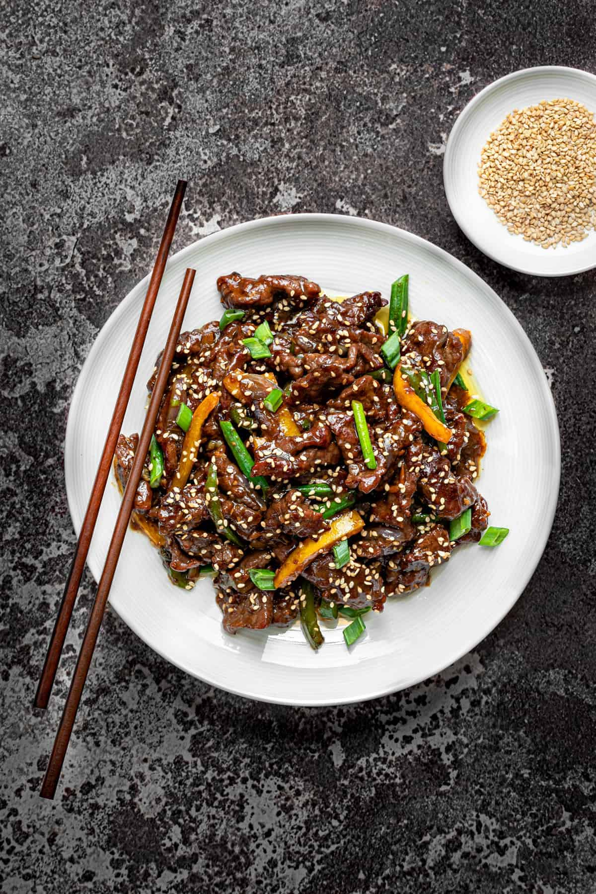 Chinese Beef stir fry in a white bowl with wooden chopsticks on a grey background