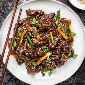 Chinese Beef stir fry in a white pasta bowl with wooden chopsticks on a grey background