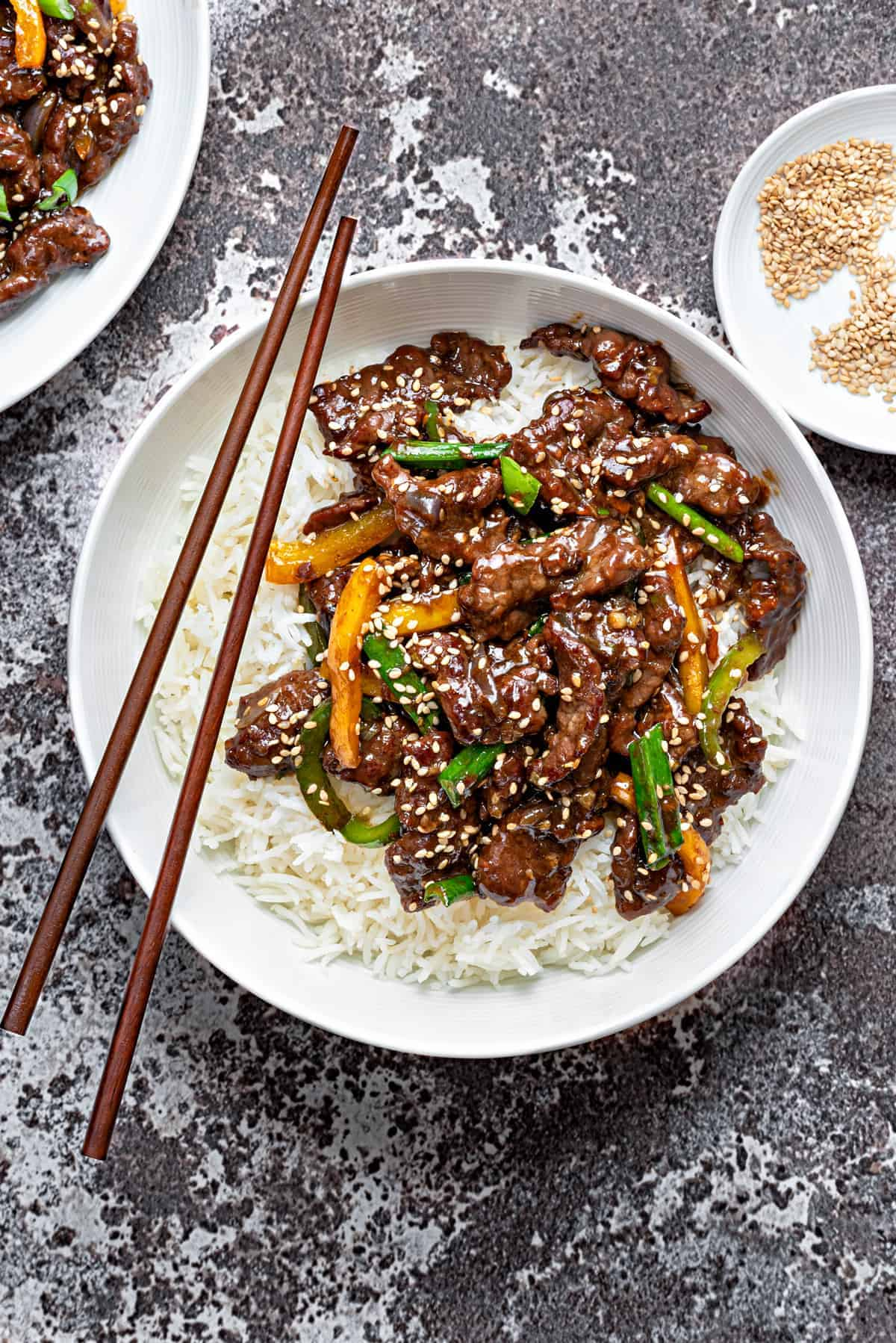 Chinese style beef stir fry over white rice in a white bowl with wooden chopsticks