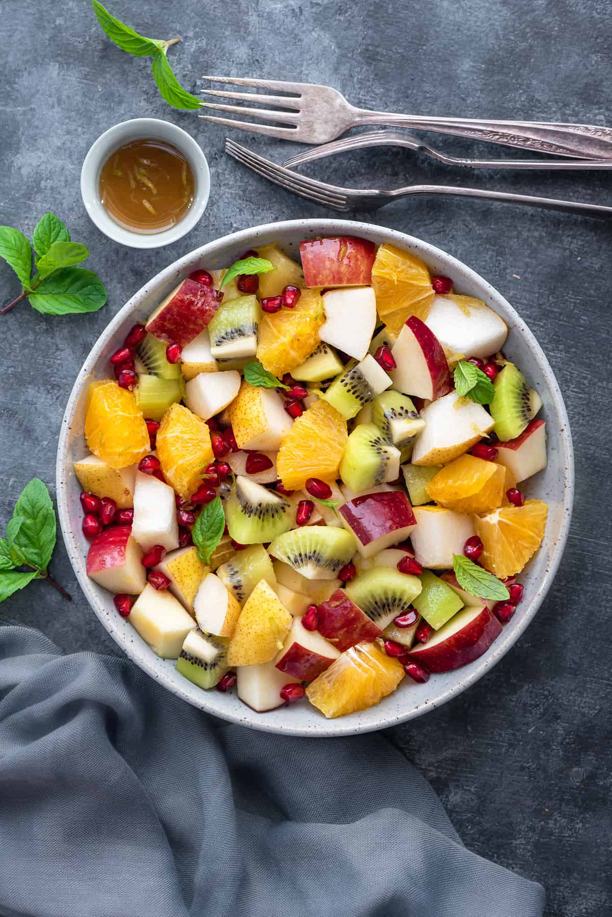 overhead shot of winter fruit salad in a white bowl on a grey table with fresh mint leaves