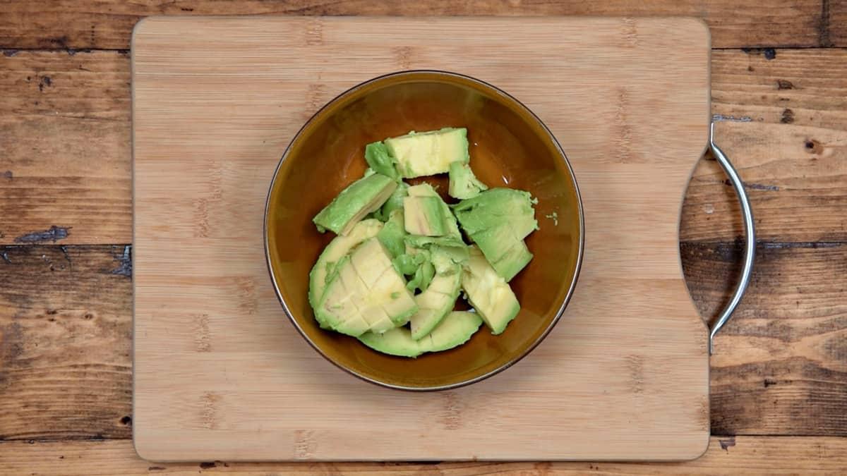 cubed avocado in a bowl on a cutting board