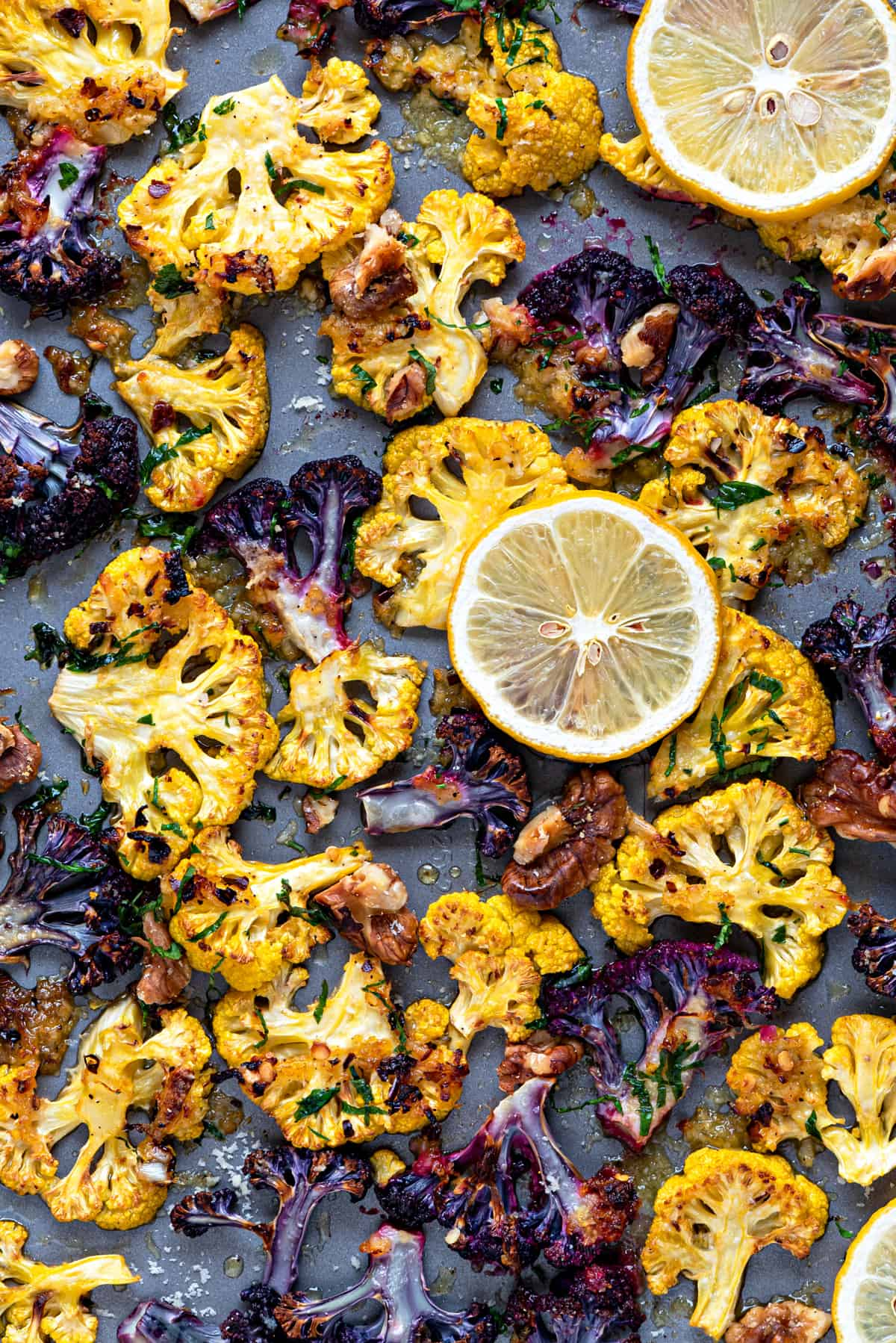 close up shot of orange and purple roasted cauliflower parmesan on a sheet pan with walnuts