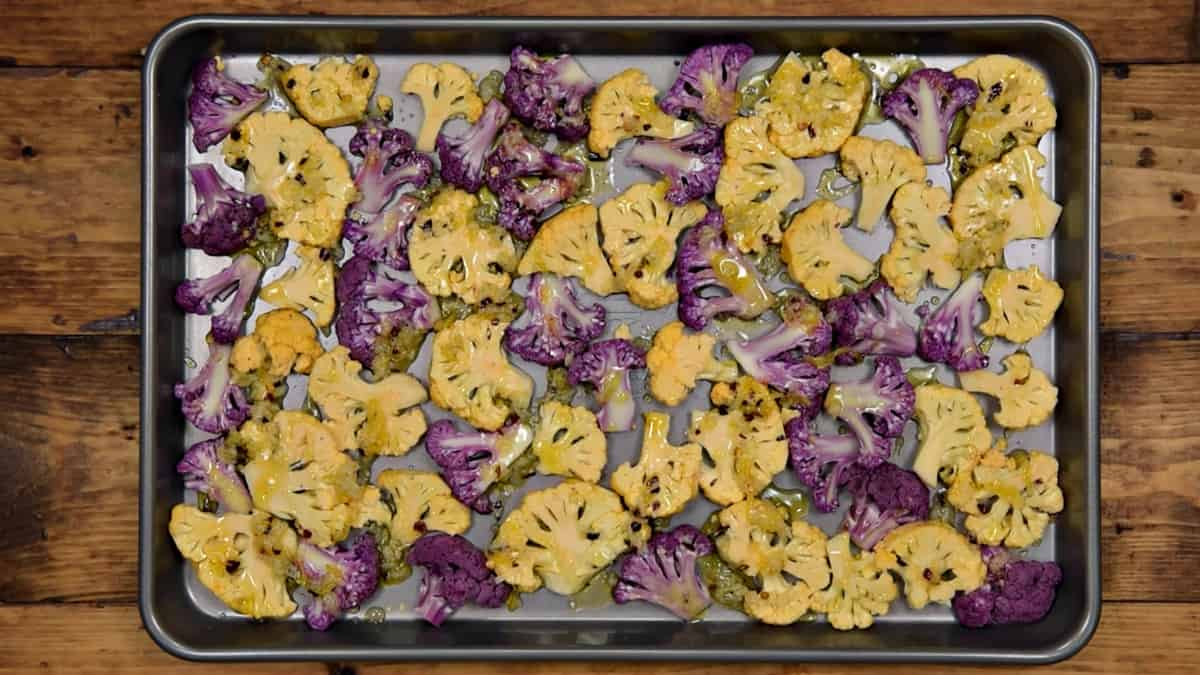 orange and purple cauliflower floret slices on a sheet pan drizzled with red pepper and garlic dressing