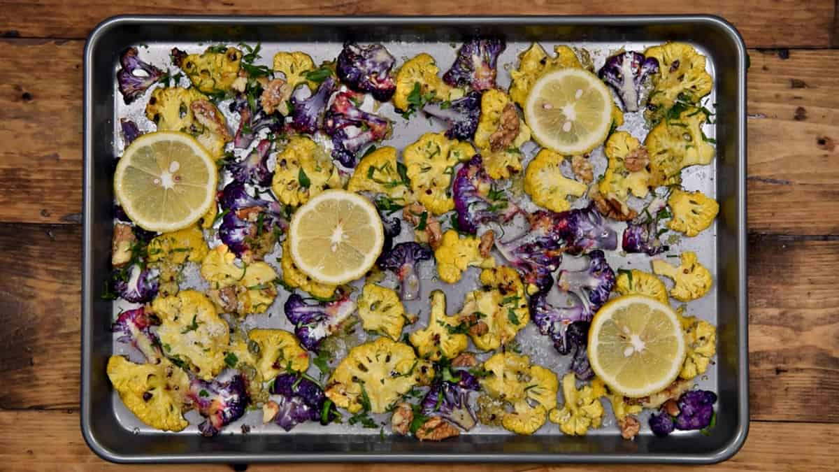 colored cauliflower florets after first bout of roasting topped with lemon slices, parmesan, parsley and walnuts