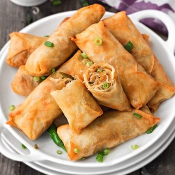 Pile of vegetable spring rolls on a white plate garnished with green onions