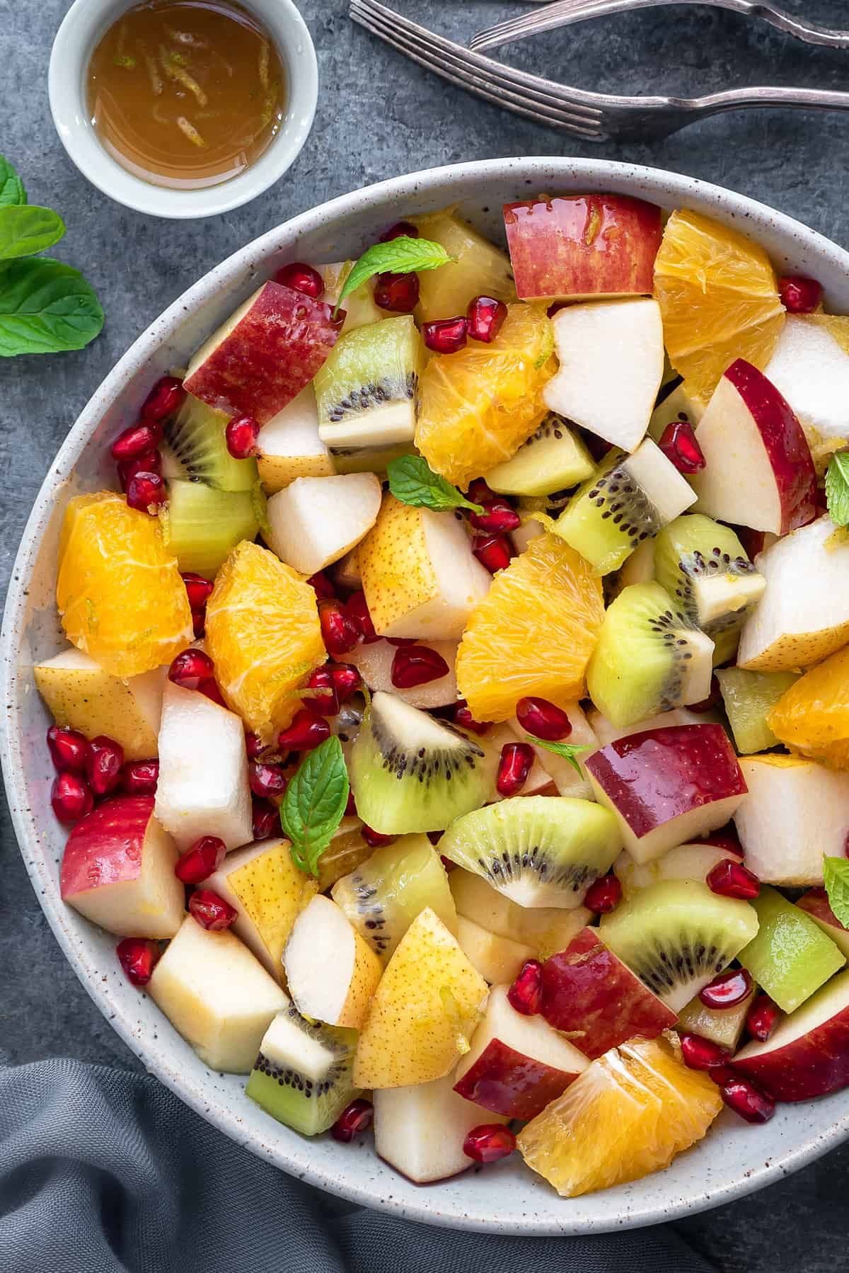 Close up shot of winter fruit salad garnished with fresh mint leaves in a white bowl