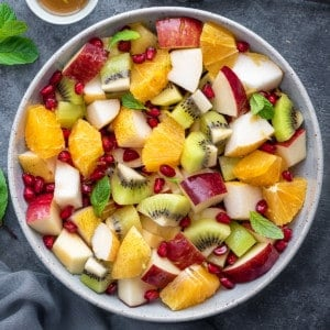 winter fruit salad garnished with fresh mint leaves in a white bowl