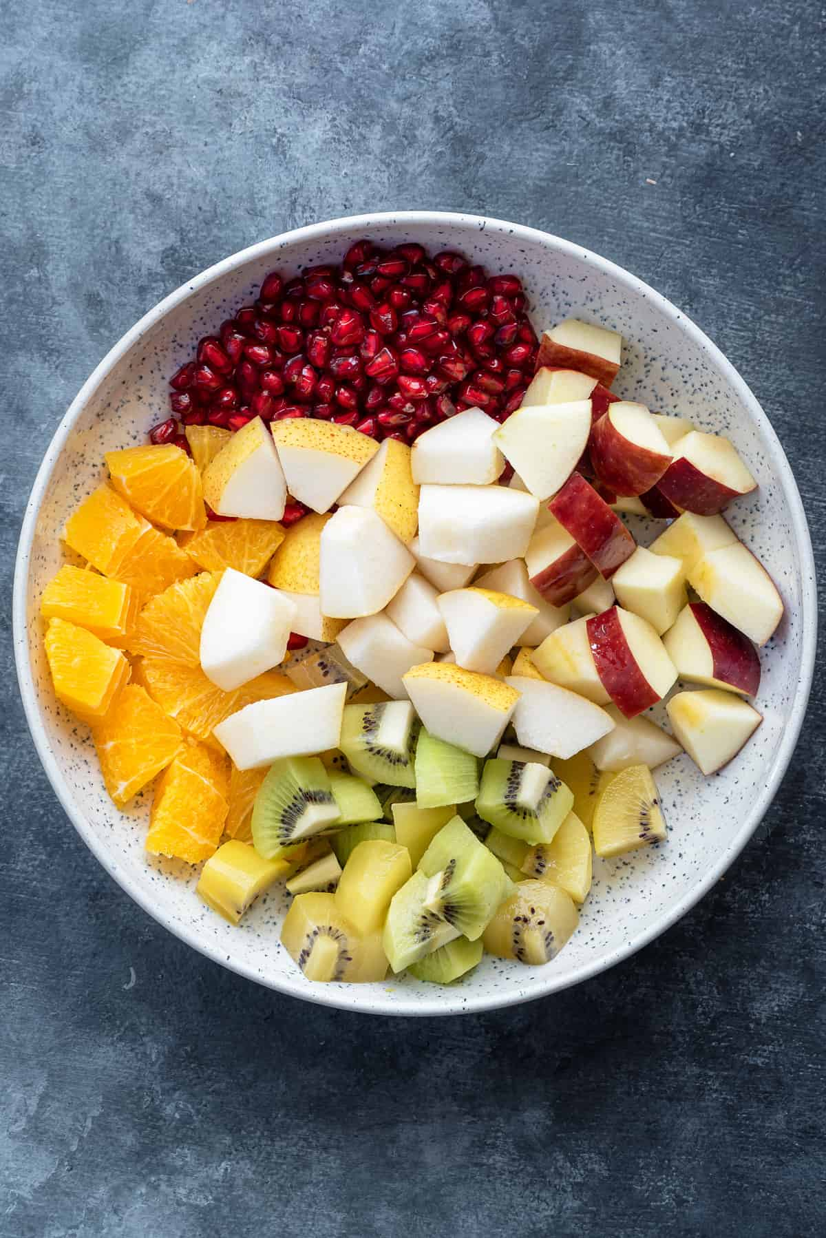 pomegranate arils, orange, pear, apple and kiwi cubes in a white speckled serving bowl