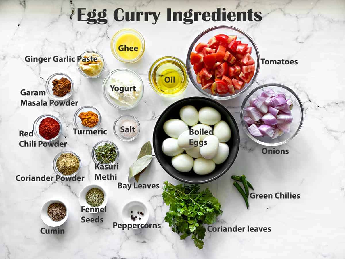 ingredients in glass bowls laid out on white table for making egg curry recipe