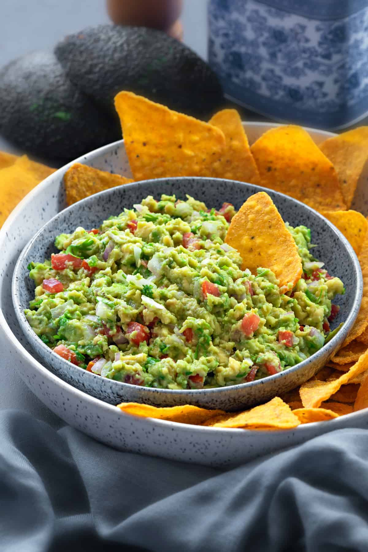 close up of a bowl filled with homemade guacamole with a platter of yellow tortilla chips