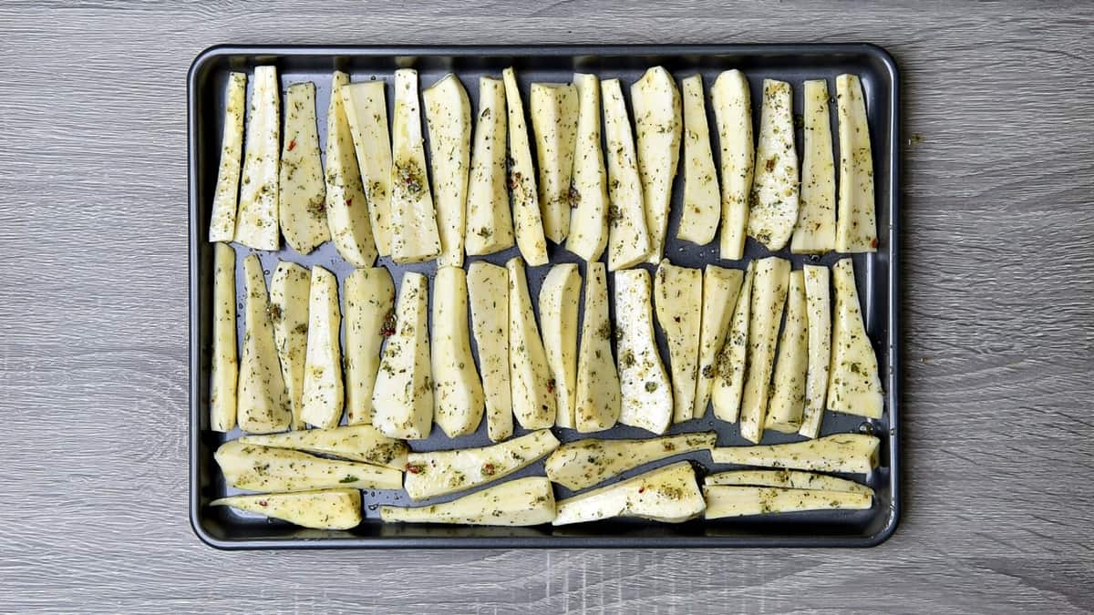 parsnip batons lined up in neat rows on a baking sheet for roasting