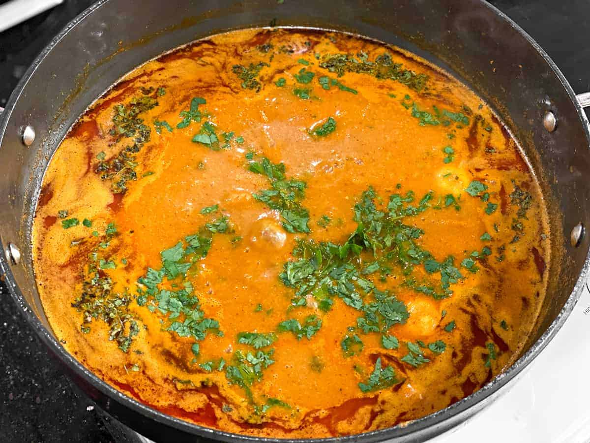 eggs simmering in curry sauce with cilantro and dried fenugreek
