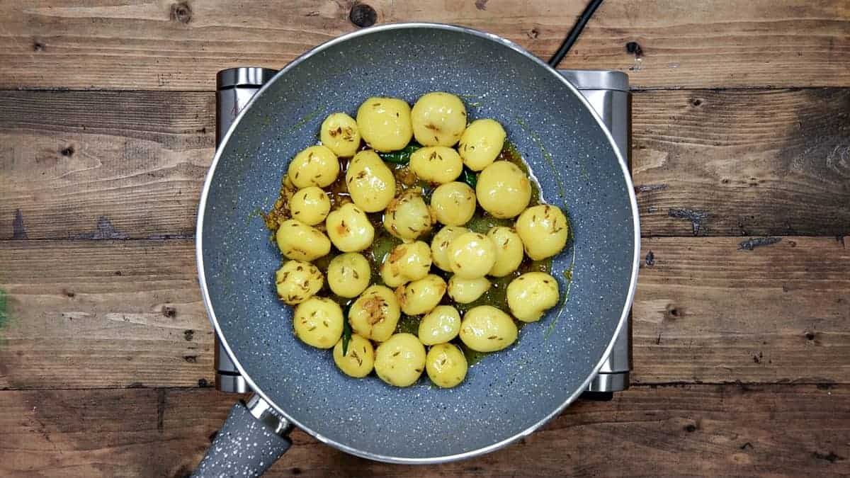 boiled and peeled baby potatoes, and salt added to the pan