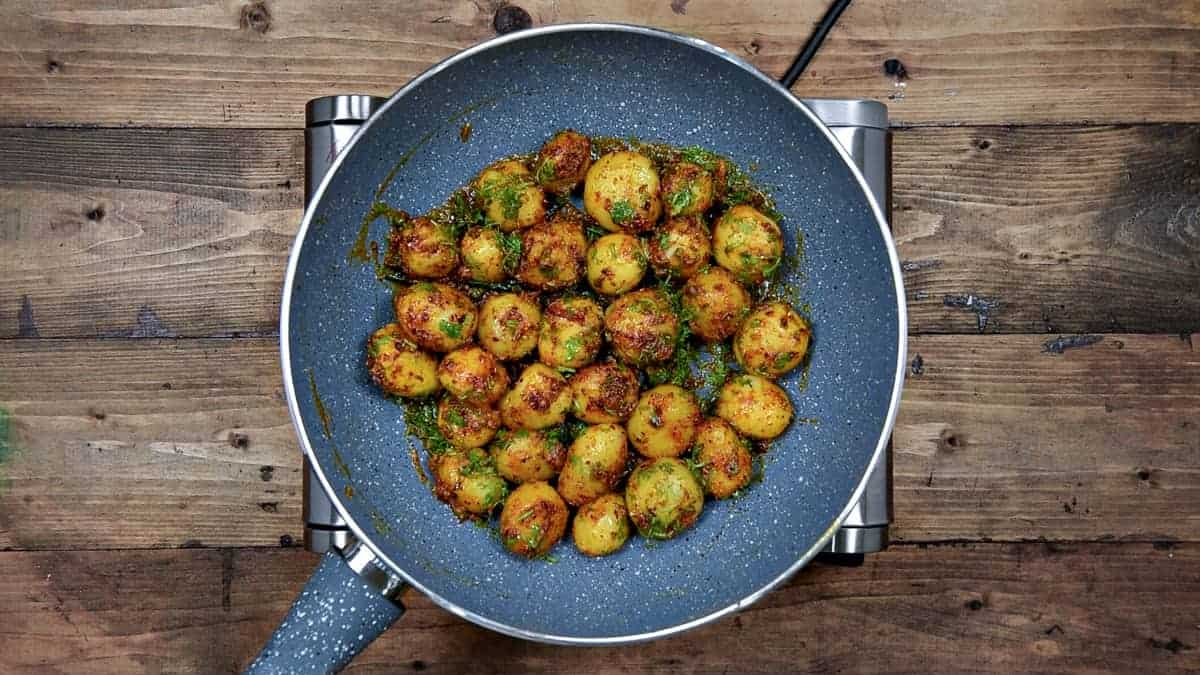 Cooked jeera aloo tossed with lime juice and fresh chopped cilantro in pan