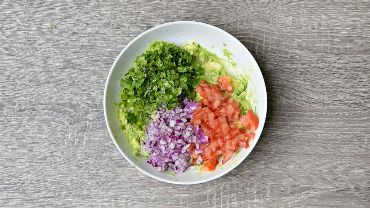 cilantro, red onion and tomato added to bowl with mashed avocado