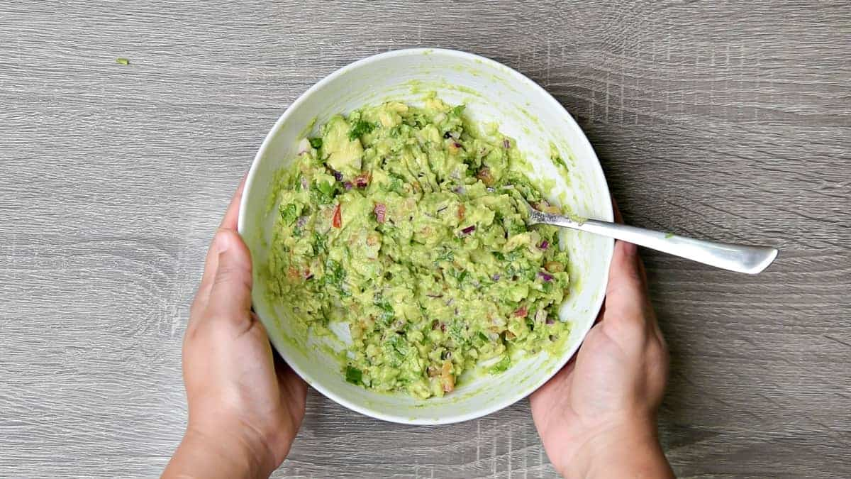 hands holding white bowl with completed recipe for guacamole recipe