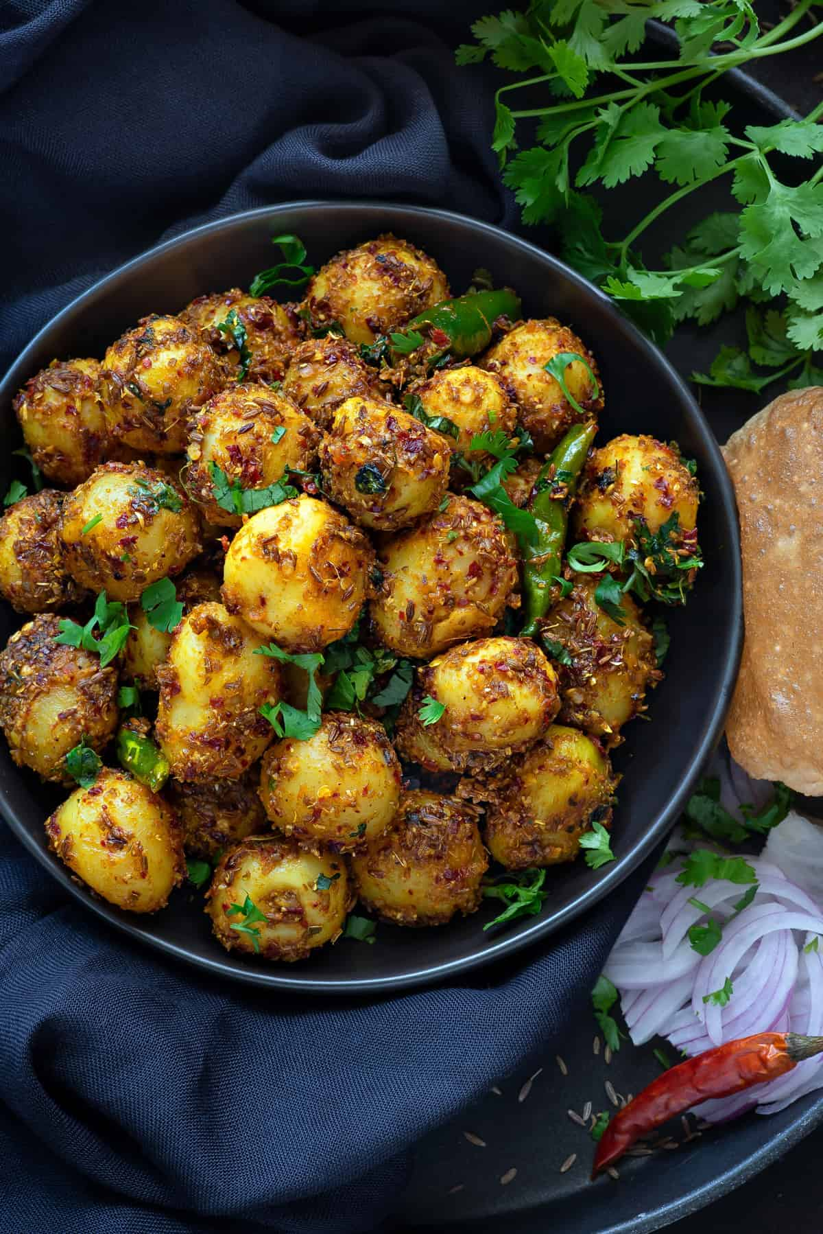 Close up of Jeera aloo served on round earthenware with sliced onions and chili on side